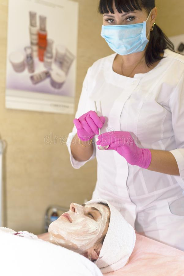 Girl at the reception at the beautician makes facial cleansing royalty free stock image
