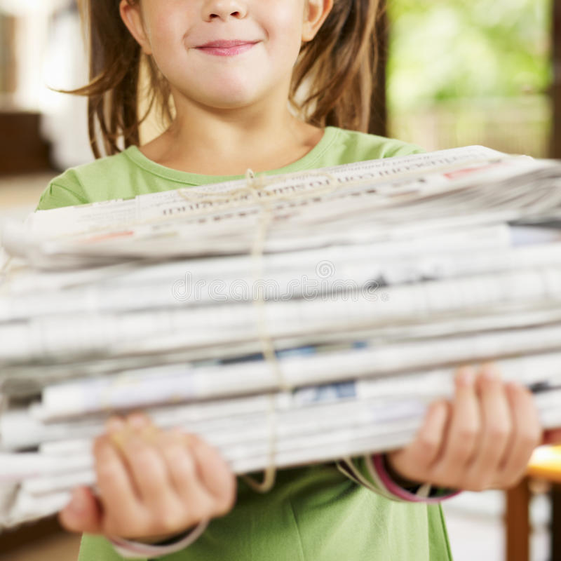 Girl recycling newspapers royalty free stock image