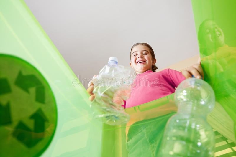 Girl recycling plastic bottles. Girl holding plastic bottles for recycling, viewed from inside recycling bin. Copy space royalty free stock image