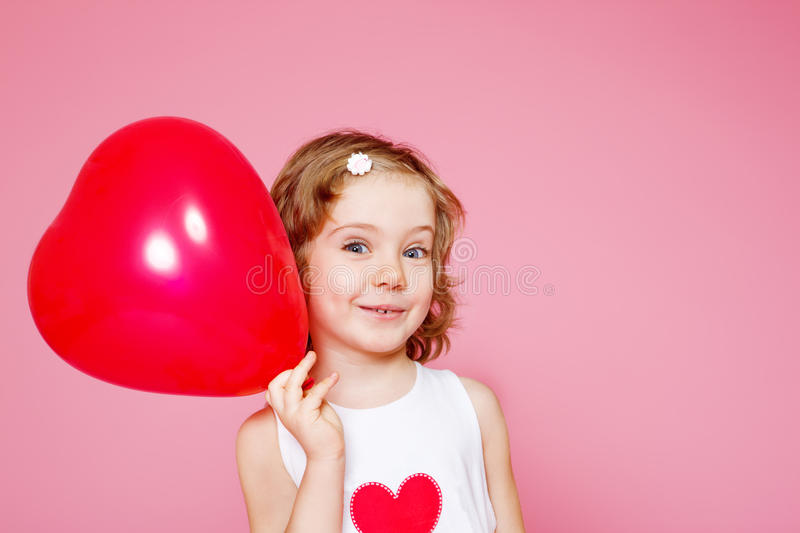 Girl with a red balloon. Portrait of a cute smiling preschool girl with a red balloon, over pink royalty free stock photography