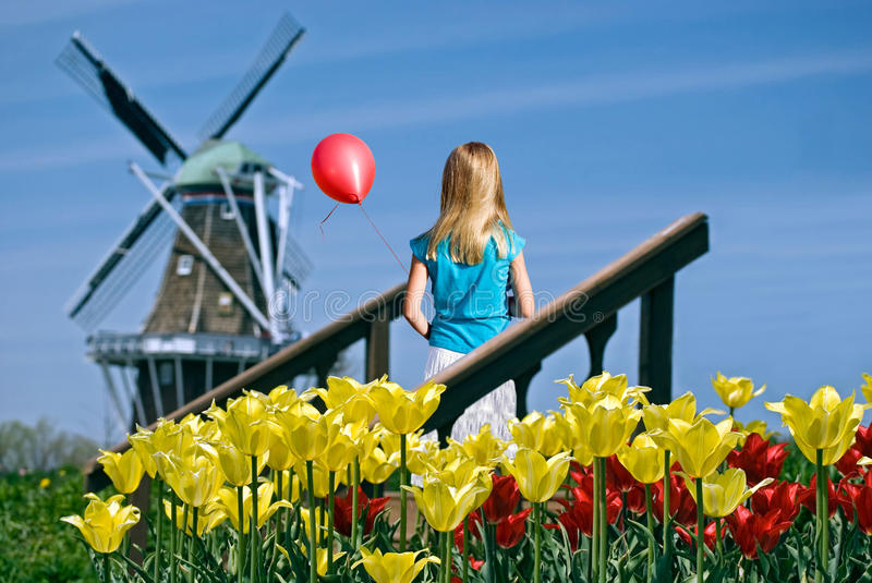 Girl with red balloon and windmill royalty free stock images