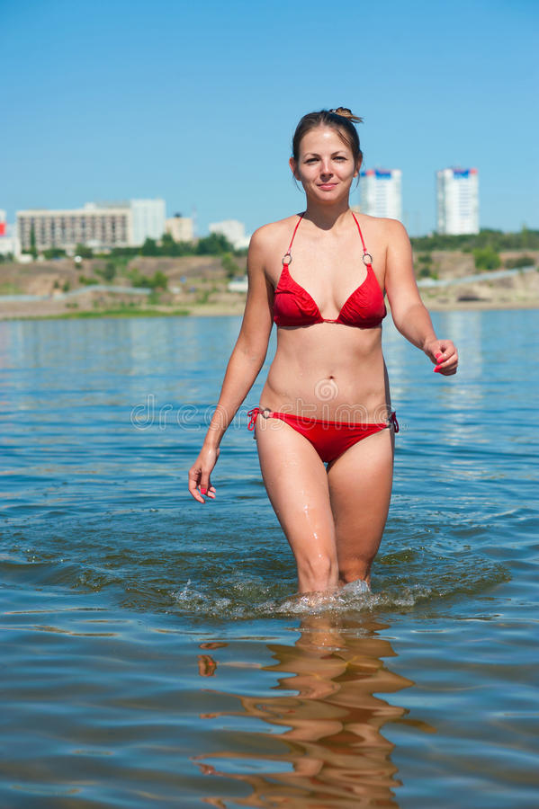 Girl in red bikini exit from river stock photography