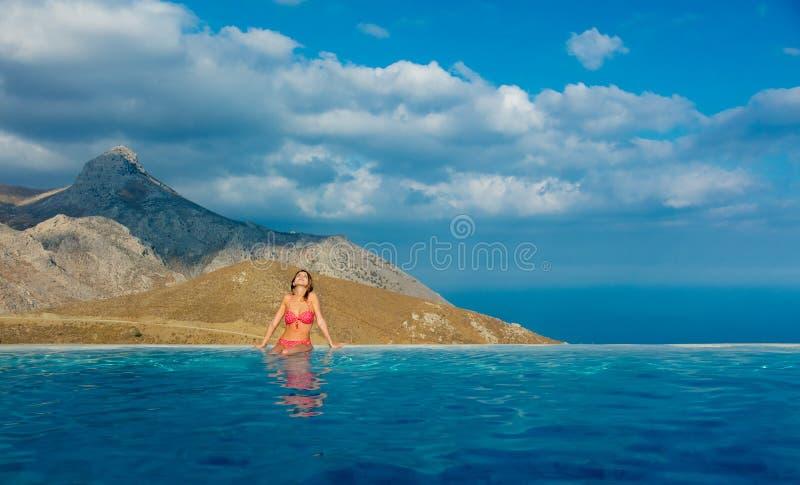 Girl in red bikini in pool with sea and mountain stock photo