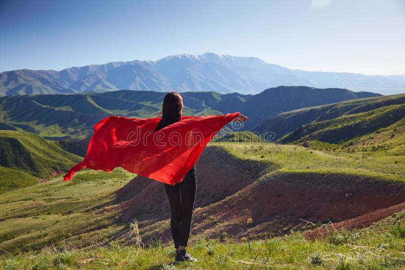 A girl with a red cape on her shoulders against the background of the spring mountain landscape. View from the back stock image