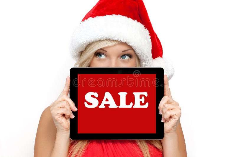 Girl in a red Christmas hat holding tablet stock photography