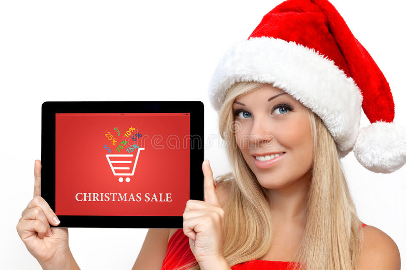 Girl in a red Christmas hat on New Year holding tablet with christmas sale on a screen. Blonde girl in a red Christmas hat on New Year, holding tablet computer stock photos