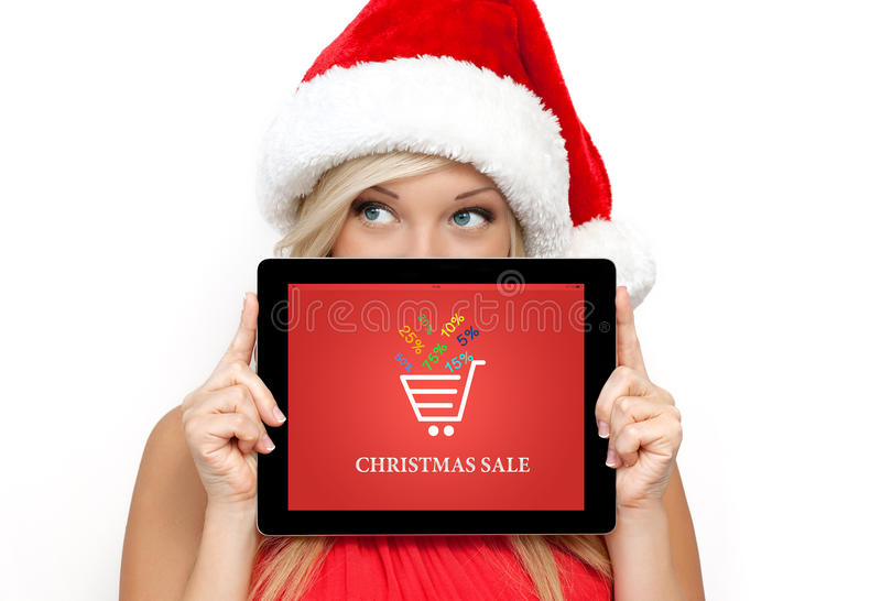 Girl in a red Christmas hat on New Year holding tablet with christmas sale on a screen. Blonde girl in a red Christmas hat on New Year, holding tablet computer royalty free stock photography