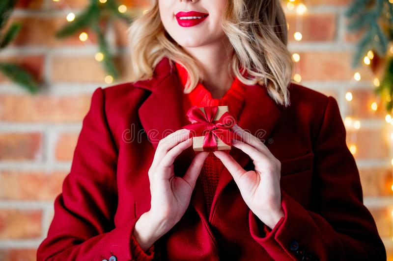 Girl in red coat with gift box stock image