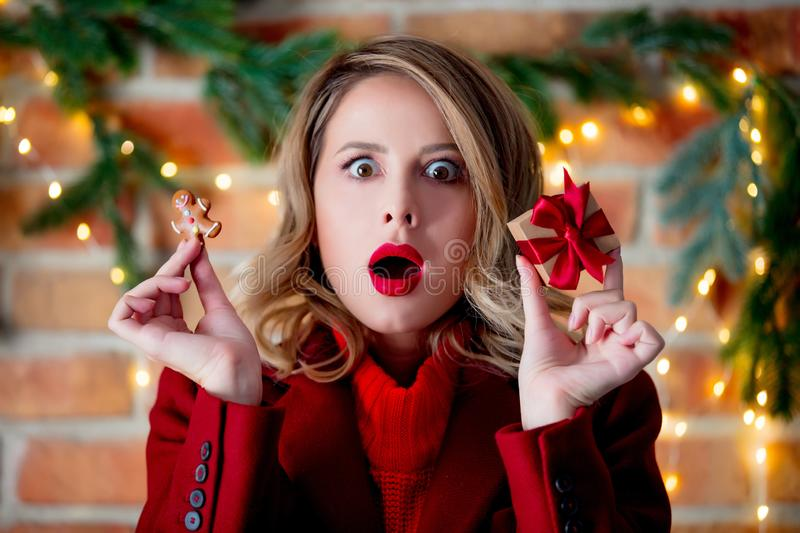 Girl in red coat with gingerbread man and gift box. Portrait of a young girl in red coat with gingerbread man and gift box at Christmas lights background stock images