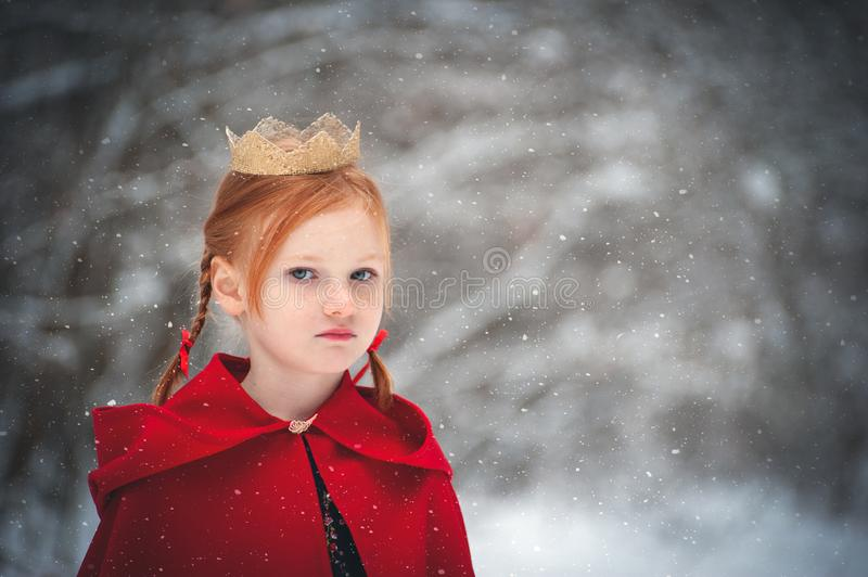 Girl in a red coat with a gold crown royalty free stock image