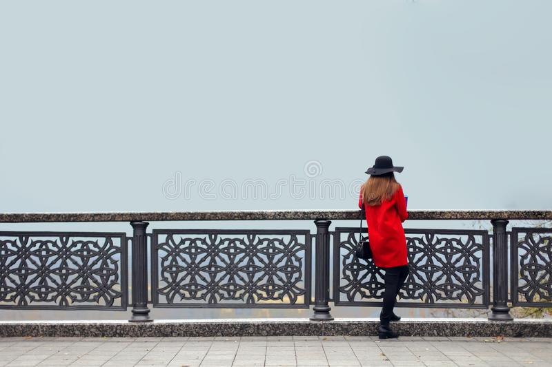 A girl in a red coat and hat, on a cold autumn morning, stands near the railing and looks into the fog. Copy space stock images