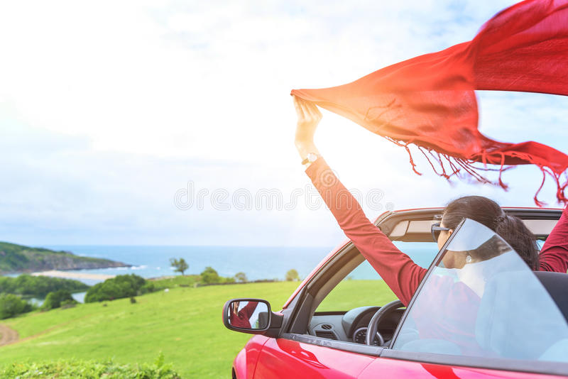Girl in a red convertible car on background seascape. stock photo