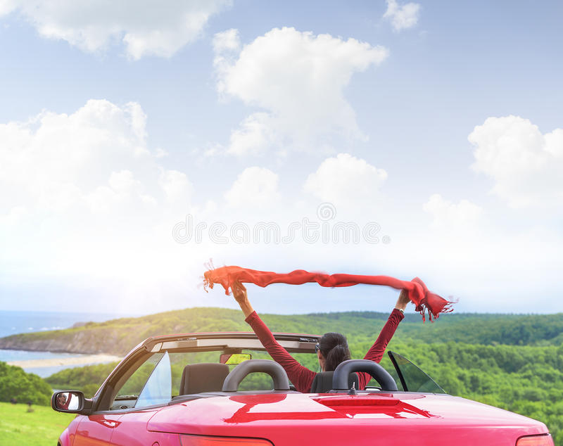 Girl in a red convertible car on background seascape. royalty free stock image