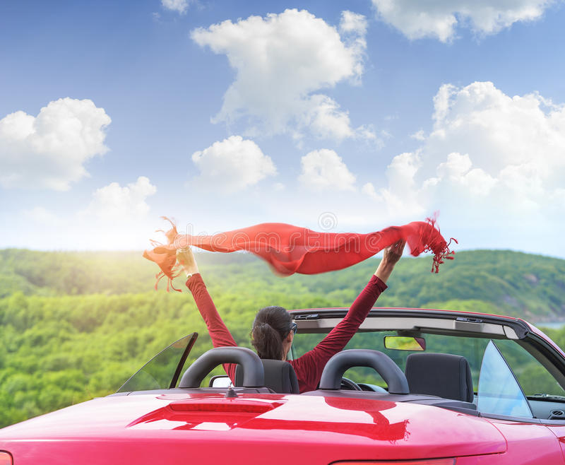 Girl in a red convertible car on background seascape. stock photos