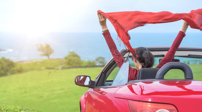 Girl in a red convertible car on background seascape. stock images