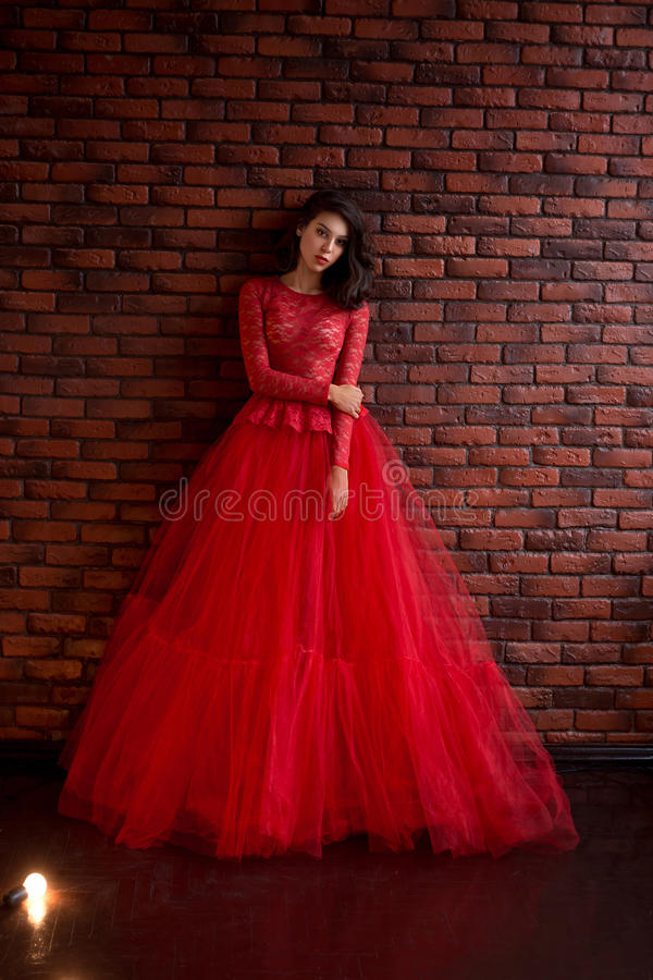 Girl in red dress. Beautiful brunette girl standing in the room. She is dressed in luxurious, lush, red dress. Woman with gentle a doll face stock photo