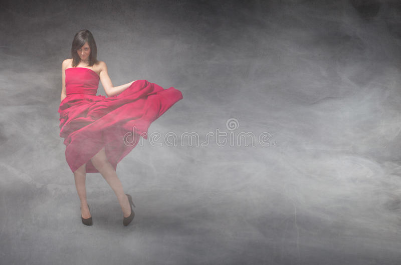 Girl in red dress. In a cloudy room royalty free stock photos