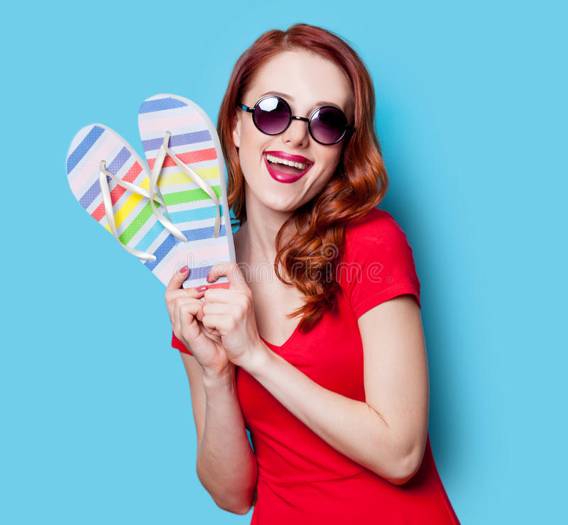Girl in red dress with flip flops. Happy redhesad girl in sunglasses with flip flops and red dress on blue background royalty free stock photography