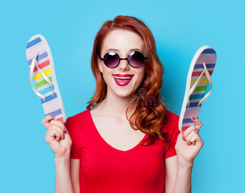 Girl in red dress with flip flops. Happy redhesad girl in sunglasses with flip flops and red dress on blue background stock photography