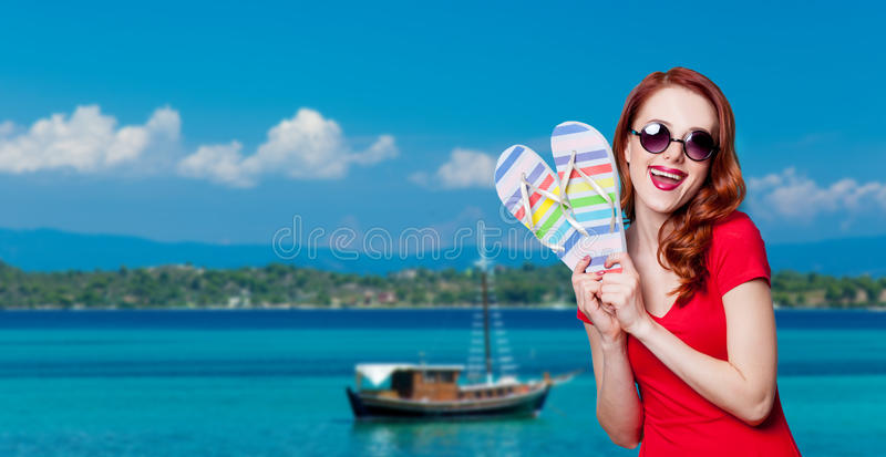 Girl in red dress with flip flops. Happy redhesad girl in sunglasses with flip flops and red dress on blue background stock photos