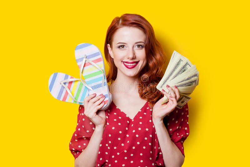 Girl in red dress with flip flops and money. Smiling redhead girl in red polka dot dress with flip flops and money on yellow background stock photography