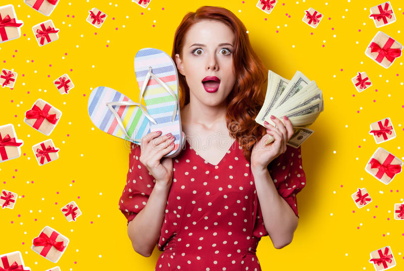 Girl in red dress with flip flops and money. Surprised redhead girl in red polka dot dress with flip flops and money on yellow background royalty free stock photography