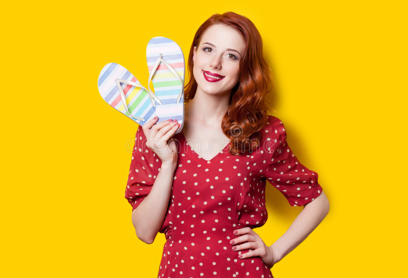 Girl in red dress with flip flops. Smiling redhead girl in red polka dot dress with flip flops on yellow background royalty free stock image