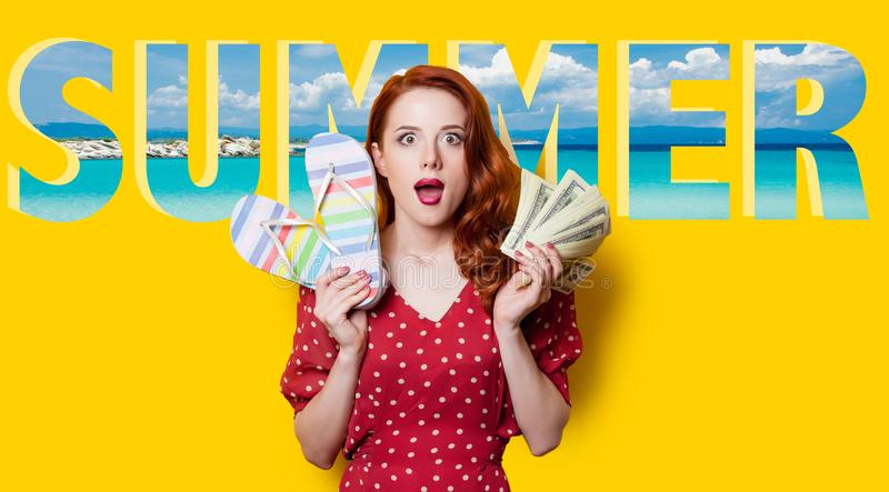 Girl in red dress with flip flops and summer word. Surprised redhead girl in red polka dot dress with flip flops sandals holding money in hand on yellow stock photography