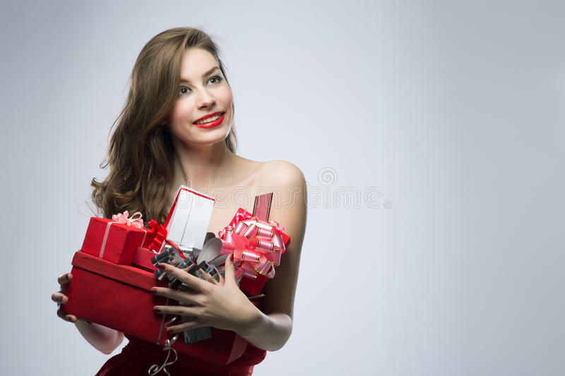 Girl in red dress with gifts on Valentines Day. Joyful girl in red dress with gifts on Valentines Day royalty free stock photos