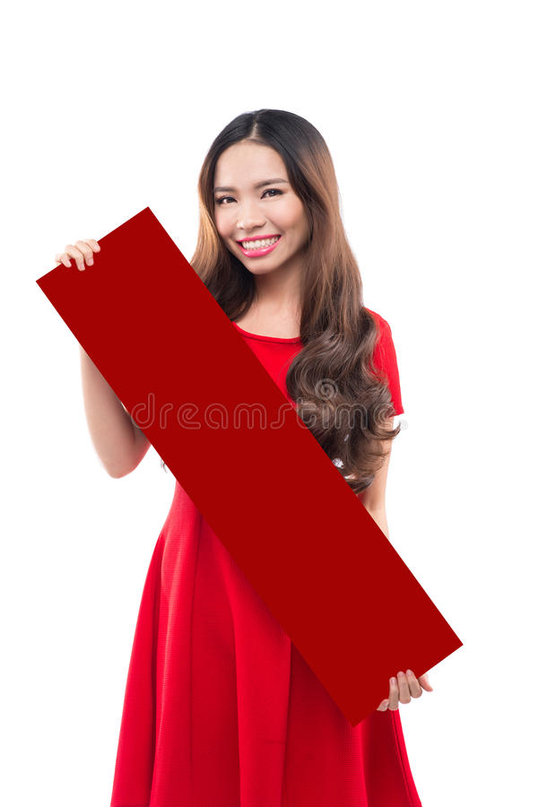 Girl in a red dress holding a piece of red paper. Beautiful girl in a red dress holding a piece of white paper royalty free stock image