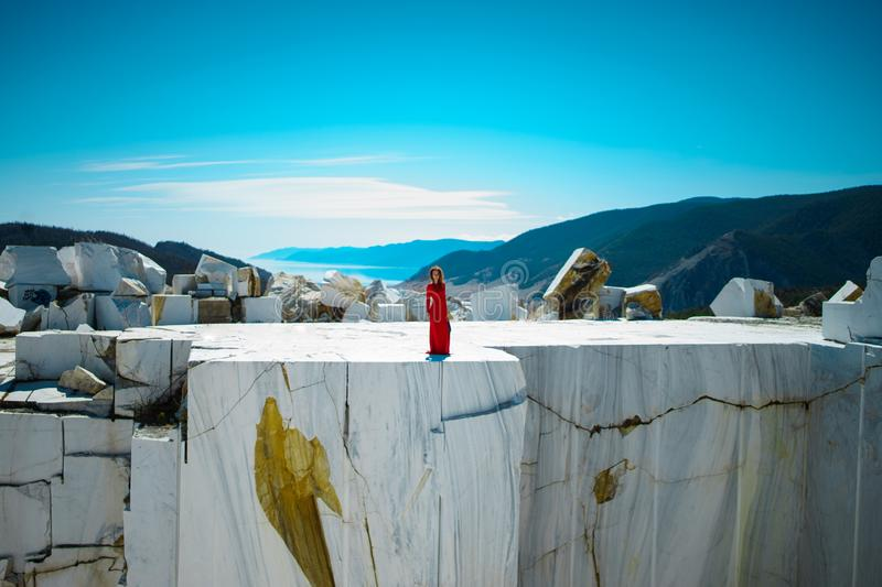 The girl in the red dress on the marble rock mountains in the background stock photo