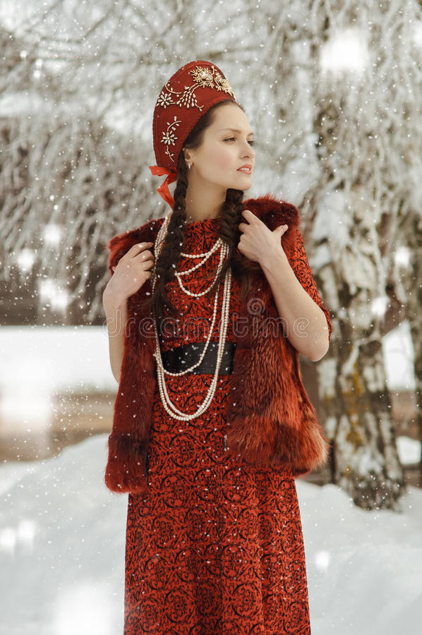 Girl in a red dress and retro folk to hat stock photo