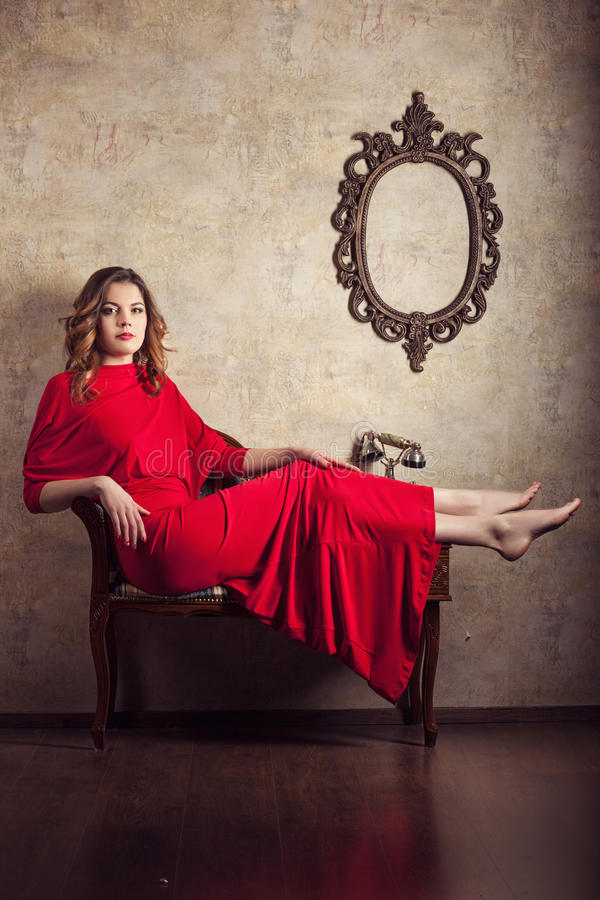 Girl in red dress sitting on a chair. Feet up stock image