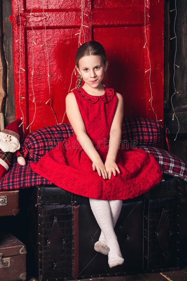 A girl in a red dress is sitting on old suitcases. royalty free stock image