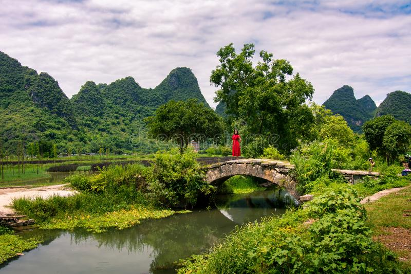 Girl in red dress stand in the old stone bridge. In Yangshuo royalty free stock photos