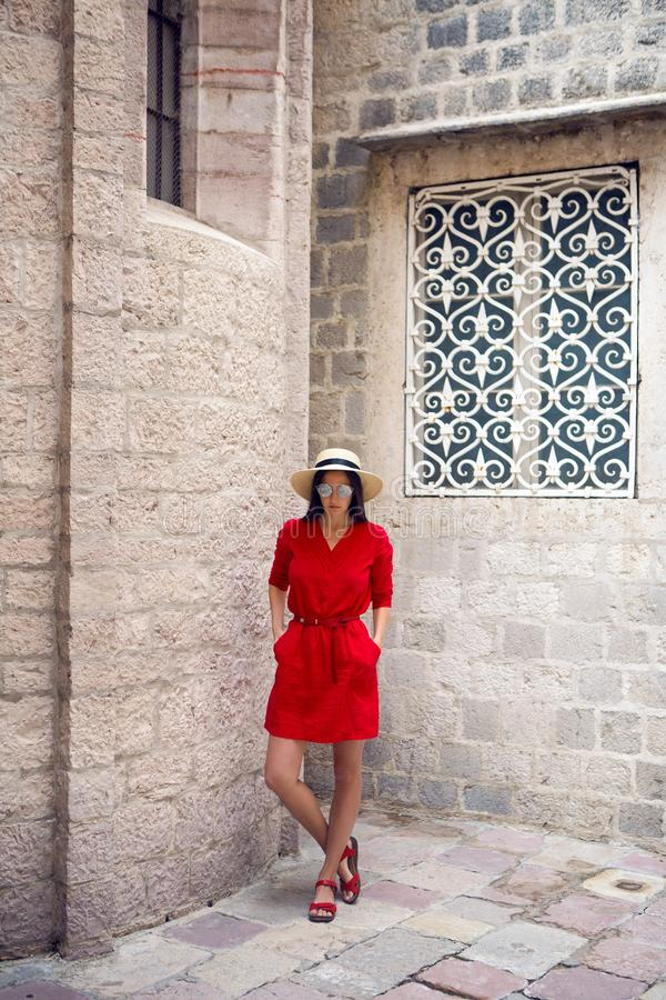 Girl in red dress standing at stone wall of the castle stock photography