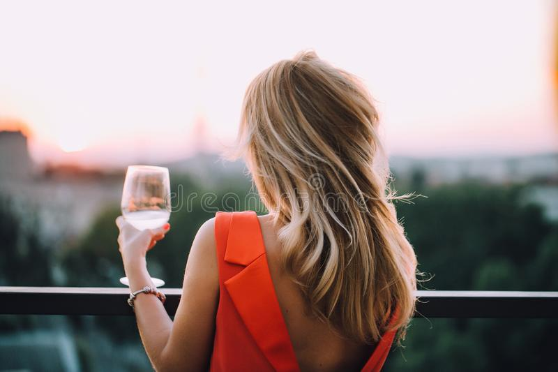 The girl in the red dress on the terrace with a glass of wine royalty free stock photography