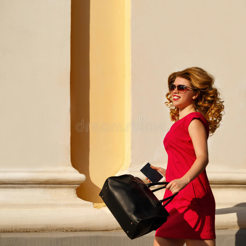Girl in red dress and with trendy bag and phone. stock image