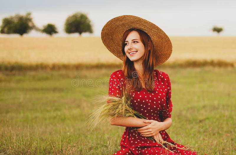Girl in red dress at wheat field royalty free stock photography