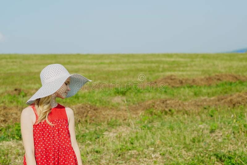 Girl in red dress and white hat with large brim stock image