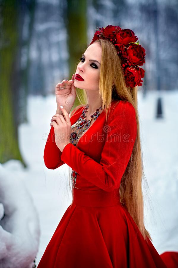 Girl in red dress in winter forest. A young girl with long hair and red flowers in her hair stock photos