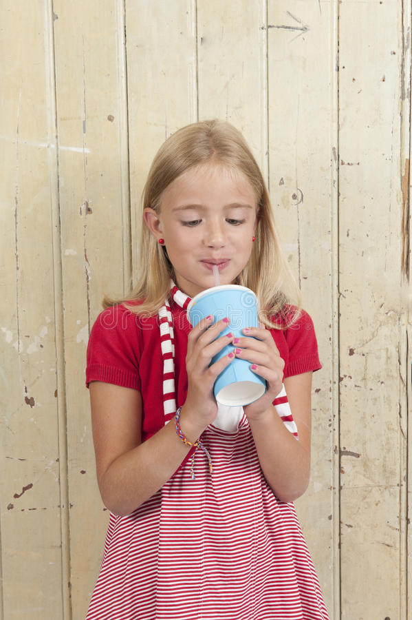 Girl in red drinking a soda royalty free stock image