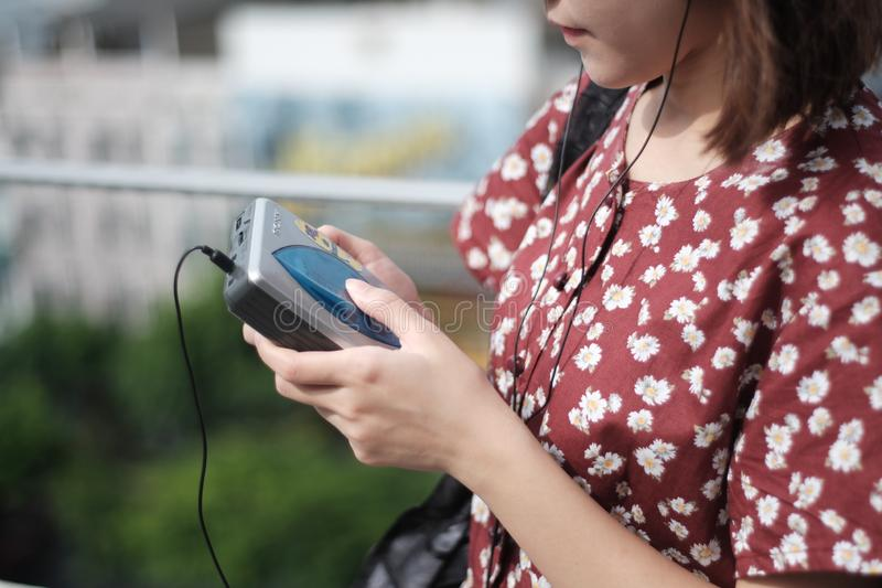 Girl and cassette tape. A girl in red flower dress listening music from cassette tape player,soft focus stock photo