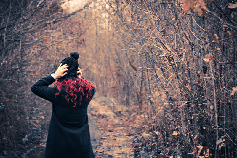Girl with red hair in black coat fixing her hat while passing trough forest stock photography
