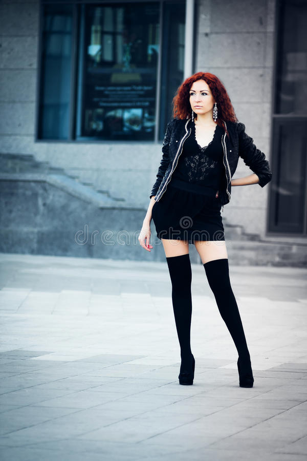 Girl with red hair. Cute girl with red hair standing on the building background royalty free stock images