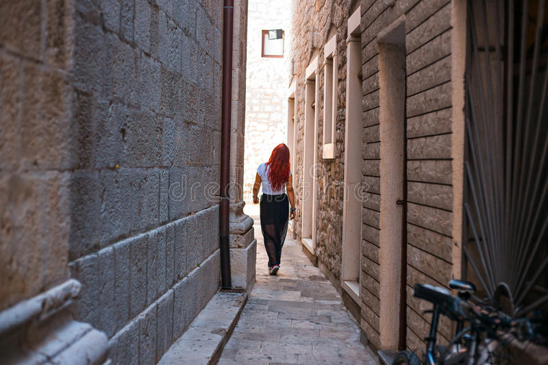 Girl with red hair in dress passing trough city tiny shallow street passage stock images