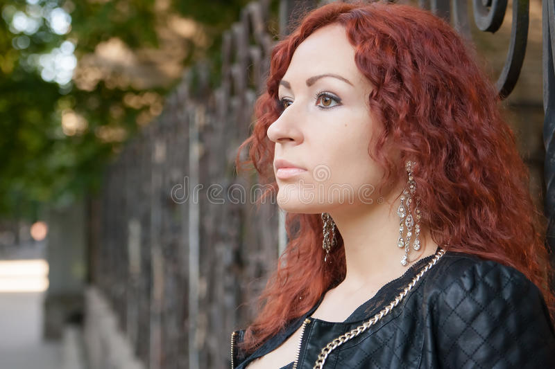 Girl with red hair on green trees alley. Portrait of a girl with red hair on city road whith green trees alley stock photo