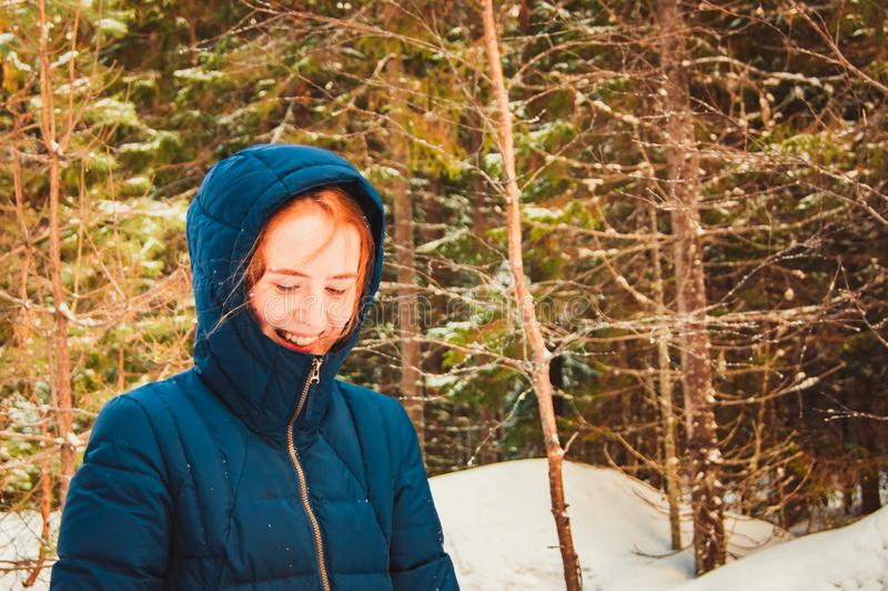 Girl with red hair in a hood in the winter forest stock images