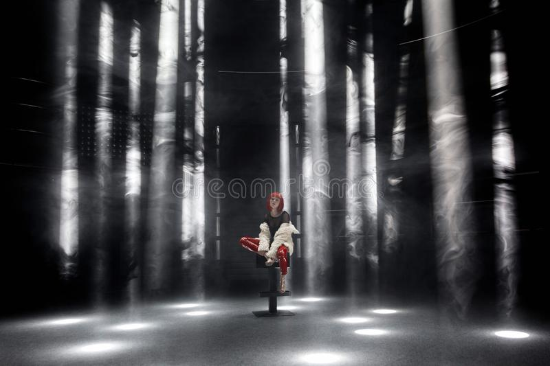 The girl with red hair in the spotlights at night club royalty free stock photography