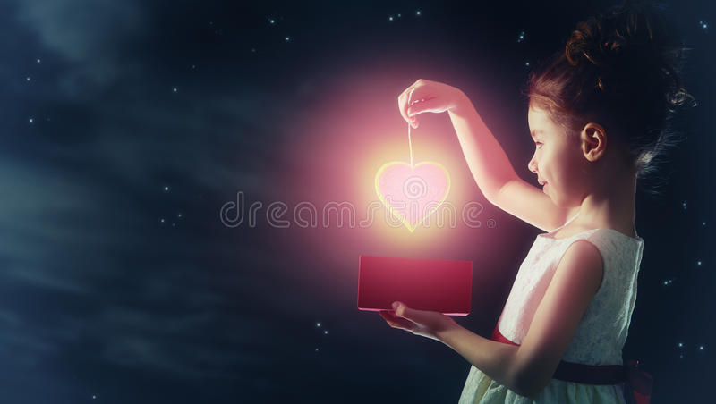 Girl with red heart. Sweet child girl with red heart. Happy little girl with gift box on background of star sky. Wedding, Valentine, celebration concept